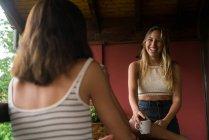 Mujeres alegres sentado con café en la terraza - foto de stock