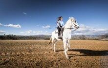 Retrato de mujer blanca montar a caballo en el campo rural en el campo - foto de stock