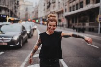 Portrait of cheerful girl with tattooed arms dancing in middle of road with traffic — Stock Photo