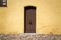 Exterior view of facade wall with old wooden door — Stock Photo
