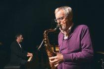 Senior spielt Saxofon mit Band — Stockfoto