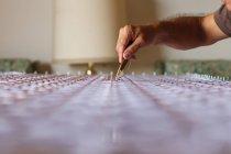 Coltivazione mano maschile che lavora con arazzo — Foto stock