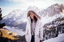 Fröhliches brünettes Mädchen in weißem Mantel bei Bergszene — Stockfoto
