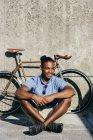 Homme souriant, assis près de bicyclette — Photo de stock