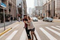 Jeune couple s'embrassant tout en marchant à travers le passage piétonnier . — Photo de stock