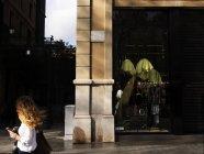 Vista lateral de hembra peatonal pasando ropa tienda en esquina - foto de stock