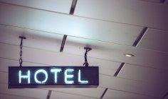 Sinal de luz de néon azul pendurado no teto — Fotografia de Stock
