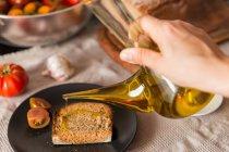 Personne versant de l'huile sur du pain grillé — Photo de stock