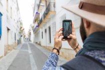 Au-dessus de l'épaule de l'homme barbu prendre des photos de rue avec smartphone . — Photo de stock