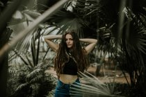 Brunette girl posing with hands behind head at botanical garden — Stock Photo