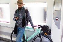 Бородатого мужчини в капелюсі, проведення fixie велосипед і перегляду смартфон в поїзді. — стокове фото