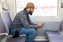 Vista laterale dell'uomo barbuto che ascolta musica con auricolari e smartphone mentre cavalca il treno . — Foto stock
