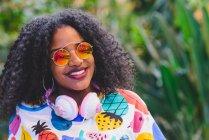 Retrato de menina sorridente em óculos de sol espelhados usando fones de ouvido em volta do pescoço — Fotografia de Stock