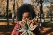 Portrait of girl hiding face with autumn chestnut leaf at park on sunny day — Stock Photo