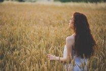 Портрет рыжеволосой девушки, позирующей на ржаном поле на закате — стоковое фото