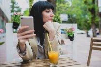 Brunette woman holding smartphone — Stock Photo