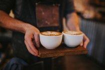 Erntehelfer mit Holzbrett und zwei Tassen Cappuccino — Stockfoto