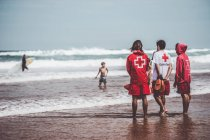 Back view of three lifesaver men in red uniform standing at beach — Stock Photo