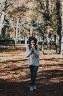 Портрет девушки, пьющей кофе в осеннем парке в солнечный день — стоковое фото