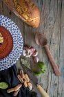 Tomato soup in patterned plate on wooden table with bread and ingredients — Stock Photo