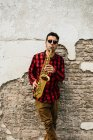 Jazzman leaning on brickwall and playing on sax — Stock Photo