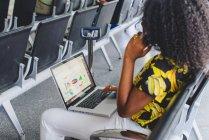 Vista lateral da mulher sentada na sala de espera e usando o laptop no colo e falando no smartphone — Fotografia de Stock