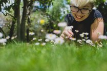 Happy girl with short hair lying on grass and looking at flowers — Stock Photo