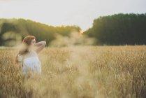 Portrait de jeune fille rousse posant sur le champ de seigle dans la lumière du coucher du soleil — Photo de stock