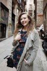 Sonriente mujer caminando por la calle - foto de stock