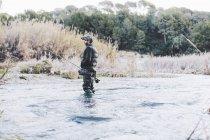 Вид збоку людини, стоячи в річку та рибалка з стрижень — стокове фото