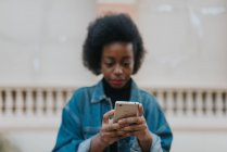 Close up view of smartphone in hands of young woman wearing denim coat at street scene — Stock Photo
