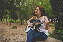 Retrato de niña pecosa sonriente sentada en piedra y tocar la guitarra en el bosque - foto de stock