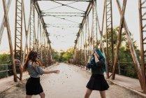 Garotas jogando confete na ponte — Fotografia de Stock