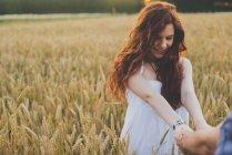 Портрет рыжеволосой девушки на ржаном поле, держащей парней за руки и смотрящей вниз — стоковое фото