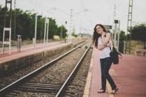 Portrait de fille aux cheveux rouges souriant sur la plate-forme ferroviaire regardant dehors pour le train — Photo de stock