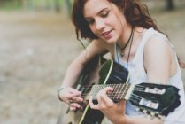 Portrait of smiling freckled girl with red hair playing guitar at woods — Stock Photo