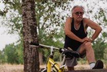Фронтальний вид літній чоловік кистей рук в парку поблизу велосипеда — стокове фото