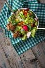 Свіжі овочевий салат в миску з хліба на тканину на дерев'яні поверхні — стокове фото