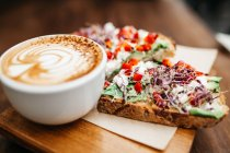 Close up view of cup of cappuccino and toasts with cream vegetables on wooden board — Stock Photo