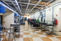 Clothing company manufacturesTANGIER, MOROCCO- April 18,2016: Industrial sewing machines in line and workers at clothing manufactures — Stock Photo