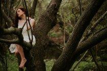 Имбирь девушка в белом платье, сидя на ветвях и прикосновения шеи — стоковое фото