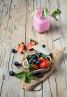 Smoothie in jar with strawberries and blueberries in bowl on wooden table — Stock Photo