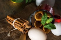 Still life of fried honey dough tubes with mint in mug lying on sacking with eggs and cinnamon sticks — Stock Photo