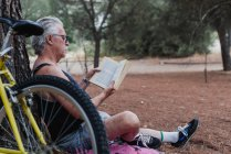 Side view of senior man reading book while sitting on ground in forest beside bicycle — Stock Photo