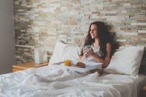 Woman with breakfast on bed — Stock Photo