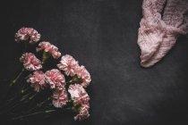Цветочный фон с розовыми гвоздиками и ткань взгляда на поверхности черного камня — стоковое фото