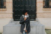 Portrait girl in coat posing with cup of coffee over building facade — Stock Photo