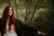 Веселый рыжая девушка позирует с вытянутыми руками в лес. — стоковое фото
