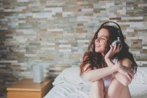 Girl sitting on bed and listening music — Stock Photo