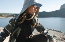 Entzückende stilvolle Frau sitzt im Sonnenlicht am Bergsee — Stockfoto